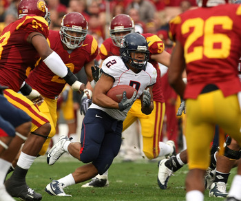 LOS ANGELES, CA - DECEMBER 05:  Running back Keola Antolin #2 of the Arizona Wildcats carries the ball against the USC Trojans on December 5, 2009 at the Los Angeles Coliseum in Los Angeles, California.  (Photo by Stephen Dunn/Getty Images)