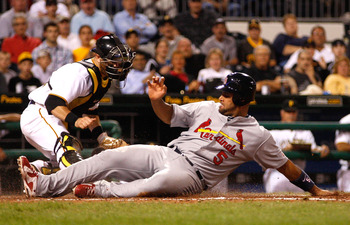 PITTSBURGH - AUGUST 23:  Albert Pujols #5 of the St Louis Cardinals slides safely and scores in front of Ryan Doumit #41 of the Pittsburgh Pirates during the game on August 23, 2010 at PNC Park in Pittsburgh, Pennsylvania.  (Photo by Jared Wickerham/Getty