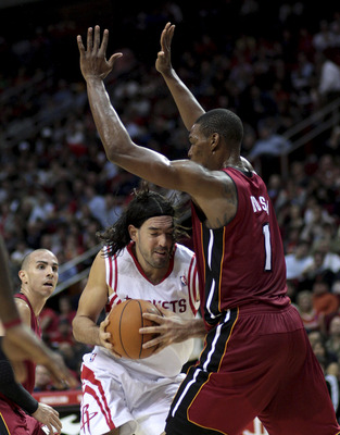 HOUSTON - DECEMBER 29: Luis Scola #4 of the Houston Rockets drives to the basket as he is fouled by Chris Bosh #1 of the Miami Heat in the third quarter at Toyota Center on December 29, 2010 in Houston, Texas.  NOTE TO USER: User expressly acknowledges an