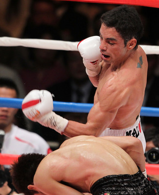 TOKYO - APRIL 30:  Fernando Montiel of Mexico hits his left on Hozumi Hasegawa of Japan during the WBC Bantamweight Title Fight between Hozumi Hasegawa and Fernando Montiel at Nippon Budokan on April 30, 2010 in Tokyo, Japan.  (Photo by Koichi Kamoshida/G