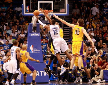ORLANDO, FL - FEBRUARY 13:  Dwight Howard #12 of the Orlando Magic attempts a shot over Pau Gasol #16 and Andrew Bynum #17 of the Los Angeles Lakers during the game at Amway Arena on February 13, 2011 in Orlando, Florida.  NOTE TO USER: User expressly ack