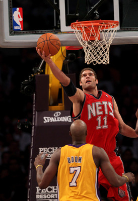 LOS ANGELES, CA - JANUARY 14:  Brook Lopez #11 of the New Jersey Nets shoots over Lamar Odom #7 of the Los Angeles Lakers at Staples Center on January 14, 2011 in Los Angeles, California. The Lakers won 100-88.  NOTE TO USER: User expressly acknowledges a