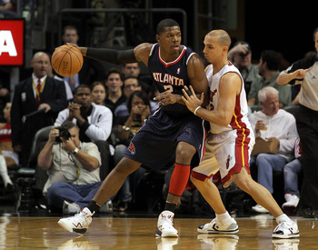 MIAMI, FL - JANUARY 18:  Joe Johnson #2 of the Atlanta Hawks posts up against Carlos Arroyo #8 of the Miami Heat during a game at American Airlines Arena on January 18, 2011 in Miami, Florida. NOTE TO USER: User expressly acknowledges and agrees that, by