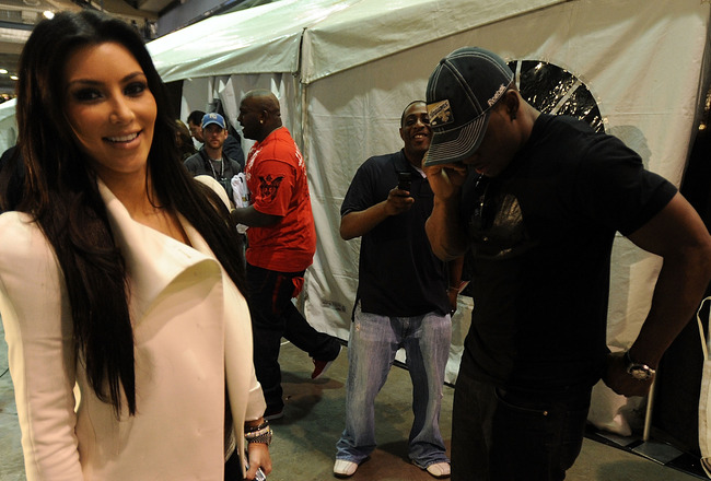 NEW ORLEANS - JANUARY 24:  Kim Kardashian looks on as her boyfriend Reggie Bush (R) of the New Orleans Saints talks on the phone after his team's victor against the Minnesota Vikings to win the NFC Championship Game at the Louisana Superdome on January 24