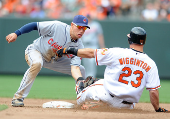 BALTIMORE - MAY 16:  Ty Wigginton #23 of the Baltimore Orioles is tagged out trying to stretch a single into a double by Asdrubal Cabrera #13 of the Cleveland Indians at Camden Yards on May 16, 2010 in Baltimore, Maryland.  (Photo by Greg Fiume/Getty Imag