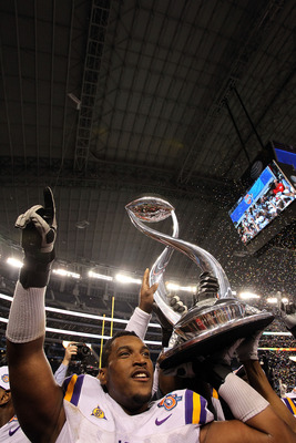 ARLINGTON, TX - JANUARY 07:  Joseph Barksdale #78 of the LSU Tigers holds the trophy while celebrating a 41-24 win against the Texas A&M Aggies during the AT&T Cotton Bowl at Cowboys Stadium on January 7, 2011 in Arlington, Texas.  (Photo by Ronald Martin