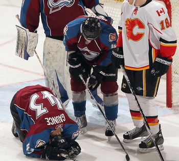 DENVER, CO - FEBRUARY 14:  Cameron Gaunce #43 of the Colorado Avalanche falls to the ice with an injury as goalie Craig Anderson #41 and John Michael Liles #4 of the Avalanche and Matt Stajan #18 of the Calgary Flames look on at the Pepsi Center on Februa