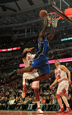 CHICAGO, IL - JANUARY 28: Brandon Bass #30 of the Orlando Magic goes up for a shot over Taj Gibson #22 and Kyle Korver #26 of the Chicago Bulls at the United Center on January 28, 2011 in Chicago, Illinois. NOTE TO USER: User expressly acknowledges and ag