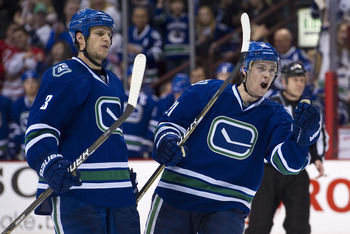 VANCOUVER, CANADA - FEBRUARY 12: Kevin Bieksa #3 and Mason Raymond #21 of the Vancouver Canucks celebrate teammate Mikael Samuelsson's #26 goal against the Calgary Flames during the second period in NHL action on February 12, 2011 at Rogers Arena in Vanco