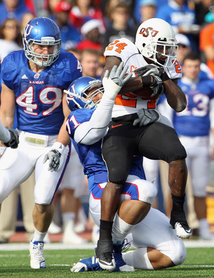 LAWRENCE, KS - NOVEMBER 20:  Running back Kendall Hunter #24 of the Oklahoma State Cowboys is pulled down by John Williams #71 of the Kansas Jayhawks during the game on November 20, 2010 at Memorial Stadium in Lawrence, Kansas.  (Photo by Jamie Squire/Get