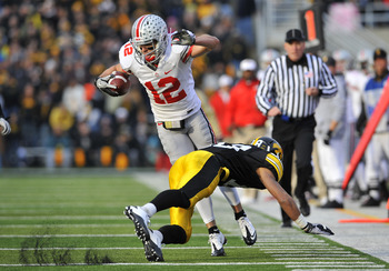 IOWA CITY, IA - NOVEMBER 20:  Defenisve back Micah Hyde #18 of the University of Iowa Hawkeyes trips up wide receiver Dane Sanzenbacher #12 of the Ohio State Buckeyes as he drove the ball down field during the first half of play at Kinnick Stadium on Nove