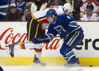 VANCOUVER, CANADA - JANUARY 22: Kevin Bieksa #3 of the Vancouver Canucks delivers a body check to Craig Conroy #24 of the Calgary Flames during the first period in NHL action on January 22, 2011 at Rogers Arena in Vancouver, British Columbia, Canada.  (Ph