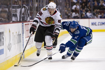 VANCOUVER, CANADA - FEBRUARY 4: Ryan Kesler #17 of the Vancouver Canucks tries to poke the puck away from Tomas Kopecky #82 of the Chicago Blackhawks during the first period in NHL action on February 04, 2011 at Rogers Arena in Vancouver, British Columbia