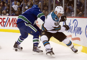 VANCOUVER, CANADA - JANUARY 20:  Ben Eager #55 of the San Jose Sharks is bumped off the puck by Christian Ehrhoff #5 of the Vancouver Canucks during the first period in NHL action on January 20, 2011 at Rogers Arena in Vancouver, BC, Canada.  (Photo by Ri