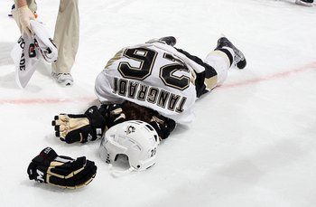 UNIONDALE, NY - FEBRUARY 11:  Eric Tangradi #26 of the Pittsburgh Penguins lays on the ice after taking a hit to the head from Trevor Gillies (not pictured) of the New York Islanders on February 11, 2011 at Nassau Coliseum in Uniondale, New York. The Isle