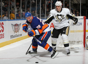 UNIONDALE, NY - FEBRUARY 11:  Zenon Konopka #28 of the New York Islanders steals the puck from Ryan Craig #23 of the Pittsburgh Penguins on February 11, 2011 at Nassau Coliseum in Uniondale, New York.  (Photo by Jim McIsaac/Getty Images)