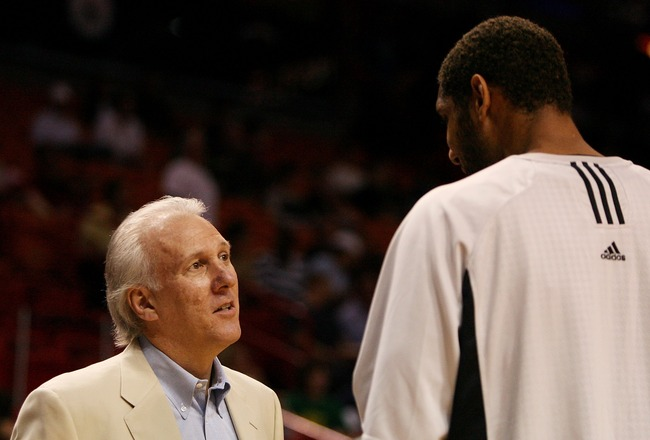 MIAMI - OCTOBER 23:  Head coach Greg Popovich of the San Antonio Spurs talks with Tim Duncan #21 prior to taking on the Miami Heat during warm-ups at American Airlines Arena on October 23,  2007 in Miami, Florida.  NOTE TO USER: User expressly acknowledge