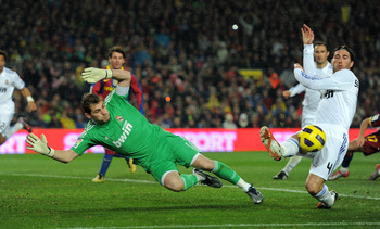 BARCELONA, SPAIN - NOVEMBER 29:  Goalkeeper Iker Casillas (L) of Real Madrid dives for a ball flanked by his teammate Sergio Ramos during the la liga match between Barcelona and Real Madrid at the Camp Nou stadium on November 29, 2010 in Barcelona, Spain.