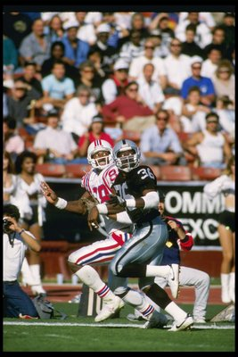 26 Nov 1989:  Defensive back Terry McDaniel of the Los Angeles Raiders (right) and New England Patriots wide receiver Hart Lee Dykes look for the ball during a game at the Los Angeles Memorial Coliseum in Los Angeles, California.  The Raiders won the game