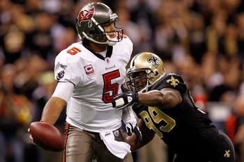 NEW ORLEANS, LA - JANUARY 02:  Quarterback Josh Freeman #5 of the Tampa Bay Buccaneers avoids a tackle by Jimmy Wilkerson #99 of the New Orleans Saints at the Louisiana Superdome on January 2, 2011 in New Orleans, Louisiana.   The Buccaneers defeated the