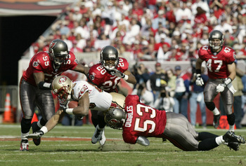 TAMPA, FL - JANUARY 12:  Wide receiver JJ Stokes #83 of the San Francisco 49ers is tackled by Derrick Brooks #55, Ronde Barber #20 and Shelton Quarles #53 of the Tampa Bay Buccaneers in the NFC Divisional Playoff game at Raymond James Stadium on January 1