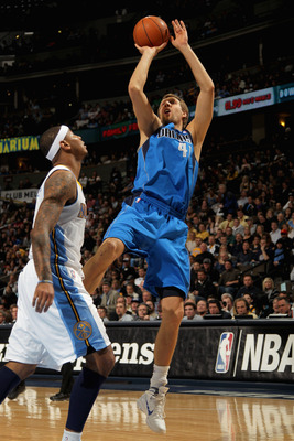 DENVER, CO - FEBRUARY 10:  Dirk Nowitzki #41 of the Dallas Mavericks takes a shot over Carmelo Anthony #15 of the Denver Nuggets during NBA action at the Pepsi Center on February 10, 2011 in Denver, Colorado. NOTE TO USER: User expressly acknowledges and