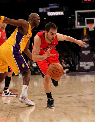 LOS ANGELES, CA - NOVEMBER 05:  Jose Calderon #8 of the Toronto Raptors drives around Lamar Odom #7 of the Los Angeles Lakers at Staples Center on November 5, 2010 in Los Angeles, California.  The Lakers won 108-102.   NOTE TO USER: User expressly acknowl