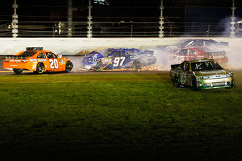 DAYTONA BEACH, FL - FEBRUARY 12:  Carl Edwards, driver of the #99 Scotts Ford, drives through the grass after crashing with Joey Logano, driver of the #20 Home Depot Toyota, Juan Pablo Montoya, driver of the #42 Target Chevrolet, and Kevin Conway, driver