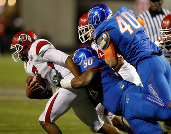 LAS VEGAS, NV - DECEMBER 22:  Quarterback Terrance Cain #7 of the Utah Utes is sacked by J.P. Nisby #50 of the Boise State Broncos as Boise State's Tyrone Crawford #40 defends during the MAACO Bowl Las Vegas at Sam Boyd Stadium December 22, 2010 in Las Ve