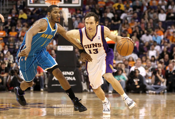 PHOENIX, AZ - JANUARY 30:   Steve Nash #13 of the Phoenix Suns drives the ball past Trevor Ariza #1 of the New Orleans Hornets during the NBA game at US Airways Center on January 30, 2011 in Phoenix, Arizona.  The Suns defeated the Hornets 104-102. NOTE T