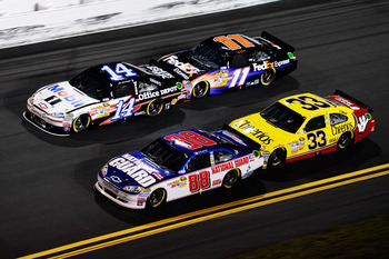 DAYTONA BEACH, FL - FEBRUARY 12:  Dale Earnhardt Jr., driver of the #88 National Guard/AMP Energy Chevrolet, races Tony Stewart, driver of the #14 Mobil 1/Office Depot Chevrolet, Clint Bowyer, driver of the #33 Cheerios Chevrolet, and Denny Hamlin, driver