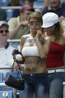 BRONX, NY - AUGUST 26:  Woman fan of the New York Yankees heading to her seat during the game against the Texas Rangers at Yankee Stadium in the Bronx, New York, on August 26, 2002. The Yankees defeated the Rangers 10-3. (Photo by Ronald Martinez/Getty Im