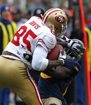 GREEN BAY, WI - DECEMBER 05: Vernon Davis #85 of the San Francisco 49ers catches a pass over Charlie Peprah #26 of the Green Bay Packers at Lambeau Field on December 5, 2010 in Green Bay, Wisconsin. The Packers defeated the 49ers 34-16. (Photo by Jonathan