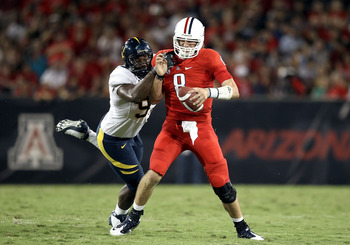 TUCSON, AZ - SEPTEMBER 25:  Quarterback Nick Foles #8 of the Arizona Wildcats is pressured as he scrambles by Cameron Jordan #97 of the California Bears during the first quarter of the college football game at Arizona Stadium on September 25, 2010 in Tucs