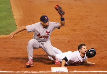 HOUSTON - OCTOBER 15:  Chris Burke #2 of the Houston Astros slides safely back into first base under the tag from Albert Pujols #5 of the St. Louis Cardinals during Game Three of the National League Championship Series at Minute Maid Park on October 15, 2