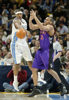 DENVER - DECEMBER 30:  Carmelo Anthony #15 of the Denver Nuggets creates a turnover against Lonny Baxter #35 of the Toronto Raptors in the first half December 30, 2003 at the Pepsi Center in Denver, Colorado.  NOTE TO USER:  User expressly acknowledges an