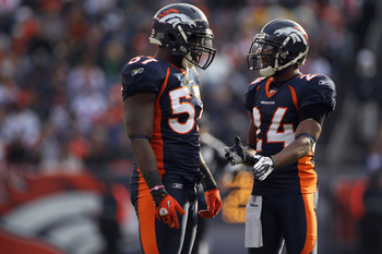 DENVER - DECEMBER 26:  Linebacker Mario Haggen #57 and cornerback Champ Bailey #24 of the Denver Broncos talk during a break in the action against the Houston Texans at INVESCO Field at Mile High on December 26, 2010 in Denver, Colorado. The Broncos defea