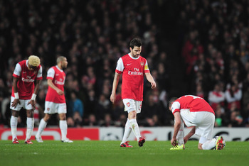 LONDON, ENGLAND - FEBRUARY 16:  Cesc Fabregas of Arsenal looks dejected after the Barcelona opening goal during the UEFA Champions League round of 16 first leg match between Arsenal and Barcelona at the Emirates Stadium on February 16, 2011 in London, Eng