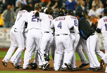 NEW YORK - SEPTEMBER 28:  Members of the New York Mets surround Ruben Tejada #11 after he hit a walk off two run double in the ninth inning to defeat the Milwaukee Brewers 4 - 3 on September 28, 2010 at Citi Field in the Flushing neighborhood of the Queen