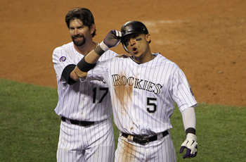DENVER - SEPTEMBER 25:  Carlos Gonzalez #5 of the Colorado Rockies breathes deep as he celebrates with Todd Helton #17 after Gonzalez scored the game winning against the San Francisco Giants on a double by Troy Tulowitzki in the 10th inning at Coors Field