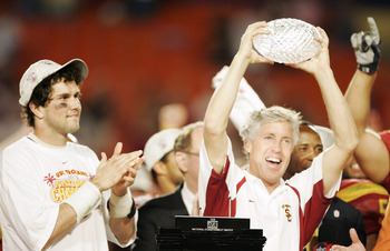 MIAMI - JANUARY 4:  Head coach Pete Carroll of the USC Trojans holds up the championship trophy as quarterback Matt Leinart #11 celebrates after defeating the Oklahoma Sooners 55-19 to win the FedEx Orange Bowl 2005 National Championship on January 4, 200
