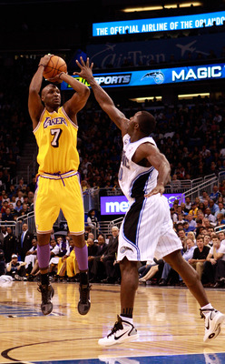 ORLANDO, FL - FEBRUARY 13:   Lamar Odom #7 of the Los Angeles Lakers attempts a shot over Brandon Bass #30 of the Orlando Magic during the game at Amway Arena on February 13, 2011 in Orlando, Florida.  NOTE TO USER: User expressly acknowledges and agrees