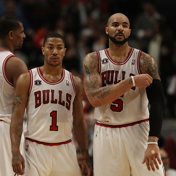 CHICAGO, IL - FEBRUARY 17: Derrick Rose #1 and Carlos Boozer #5 of the Chicago Bulls return to the court after a time-out against the San Antonio Spurs at the United Center on February 17, 2011 in Chicago, Illinois. The Bulls defeated the Spurs 109-99. NO