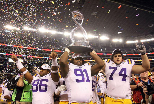ARLINGTON, TX - JANUARY 07:  (L-R) Kadron Boone #86, Chris Davenport #91 and Josh Williford #74 of the LSU Tigers hold the trophy while celebrating a 41-24 win against the Texas A&M Aggies during the AT&T Cotton Bowl at Cowboys Stadium on January 7, 2011