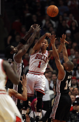 CHICAGO, IL - FEBRUARY 17: Derrick Rose #1 of the Chicago Bulls leaps to pass between Antonio McDyess #34 and Gary Neal #14 of the San Antonio Spurs at the United Center on February 17, 2011 in Chicago, Illinois. NOTE TO USER: User expressly acknowledges