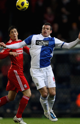 BLACKBURN, ENGLAND - JANUARY 05:  Ryan Nelsen of Blackburn Rovers heads the ball away from Fernando Torres of Liverpool during the Barclays Premier League match between Blackburn Rovers and Liverpool at Ewood park on January 5, 2011 in Blackburn, England.
