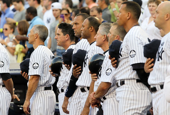 NEW YORK - JULY 16:  Derek Jeter #2 (2nd L) of the New York Yankees joins teammates and staff as they observe a moment of silence during the ceremony for owner George Steinbrenner and Yankee Stadium public address announcer Bob Sheppard before the game ag