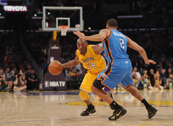 LOS ANGELES, CA - JANUARY 17:  Kobe Bryant #24 of the Los Angeles Lakers dribbles around Thabo Sefolosha #2 of the Oklahoma City Thunder at the Staples Center on January 17, 2011 in Los Angeles, California.  (Photo by Harry How/Getty Images)   NOTE TO USE