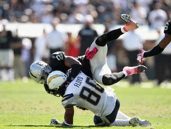 OAKLAND, CA - OCTOBER 10:  Malcom Floyd #80 of the San Diego Chargers is tackled by Michael Huff #24 of the Oakland Raiders at Oakland-Alameda County Coliseum on October 10, 2010 in Oakland, California.  (Photo by Ezra Shaw/Getty Images)