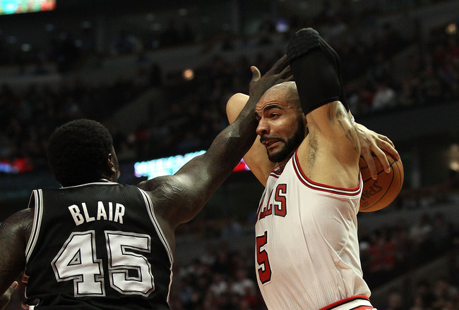 CHICAGO, IL - FEBRUARY 17: Carlos Boozer #5 of the Chicago Bulls grabs a rebound under pressure from DeJuan Blair #45 of the San Antonio Spurs at the United Center on February 17, 2011 in Chicago, Illinois. NOTE TO USER: User expressly acknowledges and ag